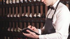 El Sommelier escribe a, poniendo la información en el suelo en productos de vino en bodega almacen de metraje de vídeo