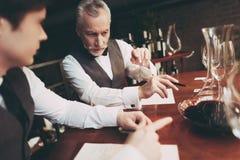 El sommelier experimentado hace que las notas sobre calidades del gusto del vino beben sentarse en restaurante fotografía de archivo libre de regalías