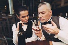 El sommelier experimentado prueba el aroma del vino del corcho en el sacacorchos en restaurante imagenes de archivo