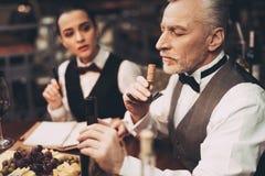 El sommelier experimentado prueba el aroma del vino del corcho en el sacacorchos en restaurante imagen de archivo libre de regalías