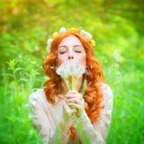 El soplar femenino hermoso en un diente de león florece Imágenes de archivo libres de regalías