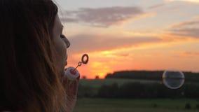 El soplo feliz de la mujer joven burbujea en la puesta del sol en la calle metrajes