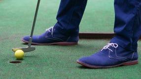 El soplo pasado en el agujero del golf, el primer, el palillo y las botas azules fotos de archivo libres de regalías