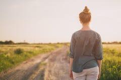 El soporte adolescente de la muchacha en el camino rural tiró de la parte posterior Foto de archivo