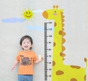 El soporte asiático feliz del niño del primer para la altura de la medida con la historieta linda en la pared de piedra de mármol fotos de archivo