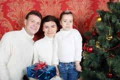 El soporte de la familia con los regalos acerca al árbol de navidad en casa. Fotografía de archivo libre de regalías