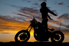 El soporte de la motocicleta de la mujer de la silueta devuelve Imagen de archivo
