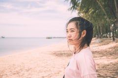 El soporte de la mujer en la playa que mira el paisaje del mar Fotos de archivo