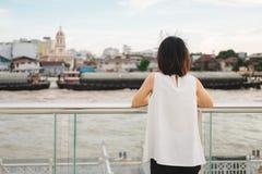 El soporte de la mujer joven solamente en la orilla y ella que mira paisaje compiten Fotografía de archivo