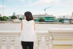 El soporte de la mujer joven solamente en la orilla y ella que mira paisaje compiten Imagenes de archivo