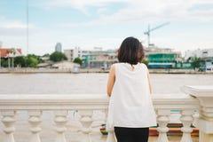 El soporte de la mujer joven solamente en la orilla y ella que mira paisaje compiten Imágenes de archivo libres de regalías