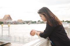 El soporte de la mujer joven solamente en la orilla y ella que mira paisaje compiten Fotografía de archivo libre de regalías