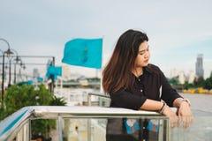 El soporte de la mujer joven solamente en la orilla y ella que mira paisaje compiten Fotos de archivo libres de regalías