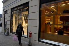 El sopper femenino camina por la tienda de Louis Vuitton Imagen de archivo