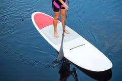 El SORBO se levanta a la mujer del tablero de paleta paddleboarding imagen de archivo