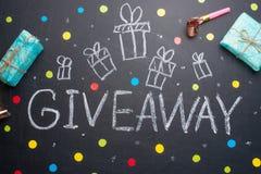El sorteo de la inscripción se escribe en una pizarra con los regalos Distribución libre, bloggers y regalos foto de archivo libre de regalías