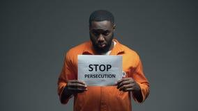 El sostenerse afroamericano del preso para la muestra de la persecución, discriminación racial almacen de metraje de vídeo