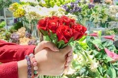El sostenerse femenino de las manos del ramo de las rosas rojas Imagen de archivo libre de regalías