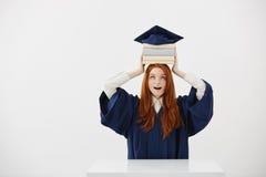 El sostenerse graduado sorprendido de la muchacha reserva en la cabeza debajo del casquillo sobre el fondo blanco Copie el espaci Fotos de archivo libres de regalías