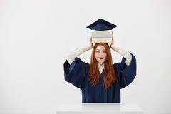 El sostenerse graduado sorprendido de la muchacha reserva en la cabeza debajo del casquillo sobre el fondo blanco Copie el espaci Imagen de archivo libre de regalías