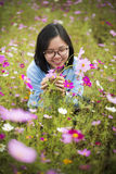 El sostenerse sonriente de la señora asiática joven florece en los prados Fotografía de archivo