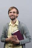El sostenerse sonriente permanente del hombre joven reserva en gris del aislante Fotografía de archivo