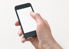 El sostenerse y tacto en el teléfono móvil con la pantalla en blanco Fotografía de archivo