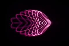 El Spirograph del laser adentro en luz roja y rosada se amplió en diversas formas del corazón Imágenes de archivo libres de regalías