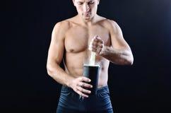 El sportman atlético delgado vierte el suplemento de la nutrición de la proteína en una coctelera plástica negra fotos de archivo