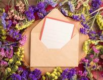 El statice multicolor secado florece alrededor de sobre con la tarjeta Fotos de archivo