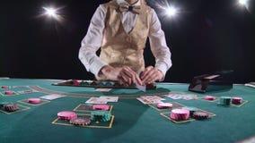 El stickman del casino en chaleco del oro toma las tarjetas del portatarjetas en la mesa de juegos Fondo negro Luz brillante lent metrajes