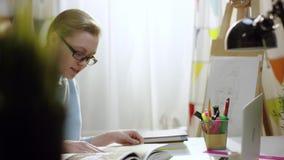 El studetn femenino examina una enciclopedia en casa almacen de metraje de vídeo