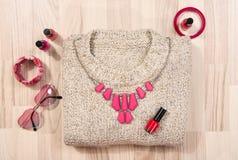 El suéter del invierno y los accesorios rosados arreglaron en el piso Fotos de archivo