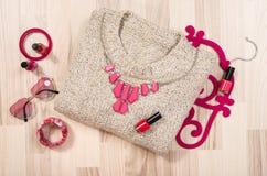 El suéter del invierno y los accesorios rosados arreglaron en el piso Fotografía de archivo