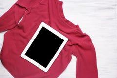El suéter y la tableta de la mujer joven en el fondo de madera blanco Imagen de archivo libre de regalías