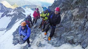 El subir atado de los escaladores atado con una cuerda con las hachas y los cascos de hielo fotos de archivo