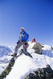 El subir de montaña de los hombres jovenes en pico nevoso Imagenes de archivo
