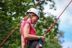 El subir practicante de la mujer bastante joven en las rocas naturales que pasan tan su ocio activo Fotografía de archivo libre de regalías