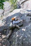 El subir practicante de la mujer bastante joven en las rocas naturales que pasan tan su ocio activo Imagenes de archivo