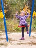 El subir sonriente de la muchacha en el oscilación en la yarda Fotografía de archivo