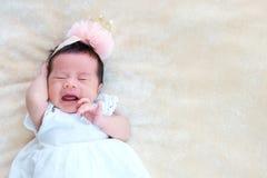 El sueño recién nacido del bebé en la cesta o en la cama y guarda sonrisa con todo el mundo Amor de la sensación el bebé y la nec imagen de archivo libre de regalías