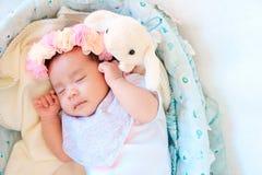 El sueño recién nacido del bebé en la cesta o en la cama y guarda sonrisa con todo el mundo Amor de la sensación el bebé y la nec imagenes de archivo