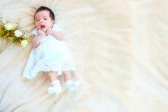 El sueño recién nacido del bebé en la cesta o en la cama y guarda sonrisa con todo el mundo Amor de la sensación el bebé y la nec fotografía de archivo