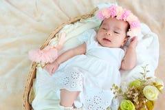 El sueño recién nacido del bebé en la cesta o en la cama y guarda sonrisa con todo el mundo Amor de la sensación el bebé y la nec imágenes de archivo libres de regalías