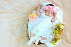 El sueño recién nacido del bebé en la cesta o en la cama y guarda sonrisa con todo el mundo Amor de la sensación el bebé y la nec foto de archivo