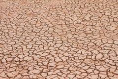 El suelo seco y la tierra agrietada profundamente agrieta la tierra en la tierra roja como símbolo del clima y de la sequía calie foto de archivo libre de regalías