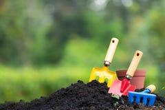 El suelo y la hortensia del jardín de las herramientas florecen en maceta sobre natur imagen de archivo