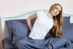 El sufrimiento de la mujer del dolor de espalda que se sienta en cama, dolor de espalda femenino en casa en el dormitorio, esta c imagen de archivo