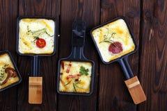 El suizo tradicional delicioso derritió el queso del raclette en la ebullición cortada en cuadritos fotos de archivo libres de regalías