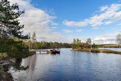El summerhouse de madera en los pequeños barcos de la isla y de navegación acerca al pequeño embarcadero en el Daugava del río Fotos de archivo libres de regalías